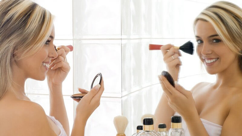 Seitenansicht blonde Frau in weißem Handtuch steht vor Badezimmerspiegel und schminkt sich