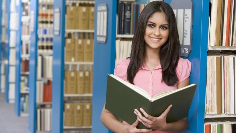 Studentin steht mit aufgeschlagenem Buch in der Bibliothek, lächelt in Kamera
