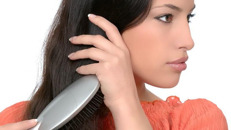 Dunkelhaarige Frau bürstet ihre langen Haare