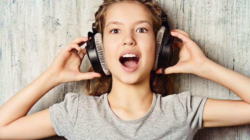 Mädchen in grauem Shirt hört Musik mit einem großen Kopfhörer und hat den Mund weit geöffnet