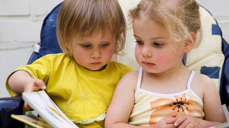 Junge im gelben Shirt und kleines Mädchen im Top lesen in einem großen Buch