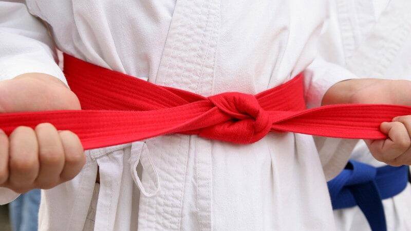 Nahaufnahme Zubinden eines roten Karategürtels
