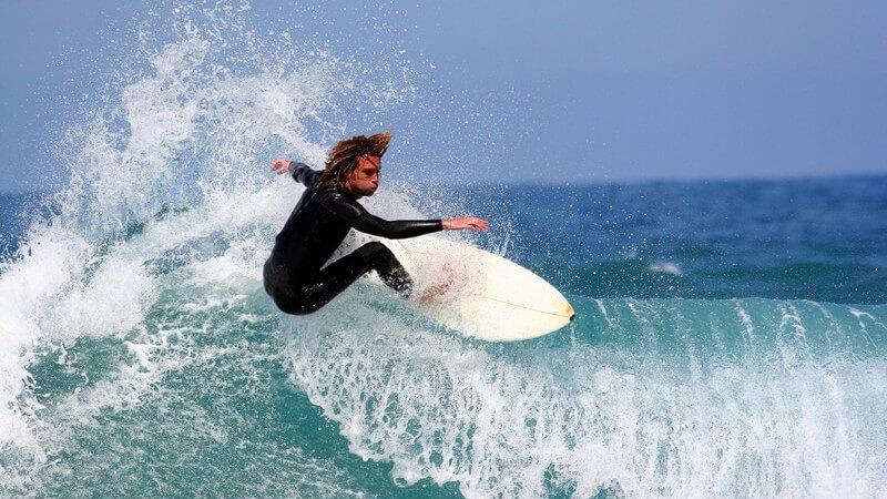 Mann in Neoprenanzug auf weißem Surfbord in einer blauen Welle