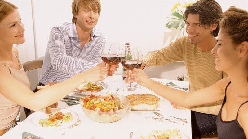 Vier Freunde stoßen bei einem Dinner mit Wein an