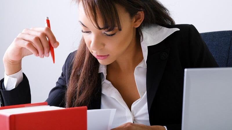Beruf - Junge Frau in Bluse und Blazer sitzt mit einem roten Kulli konzentriert vor einem roten Buch