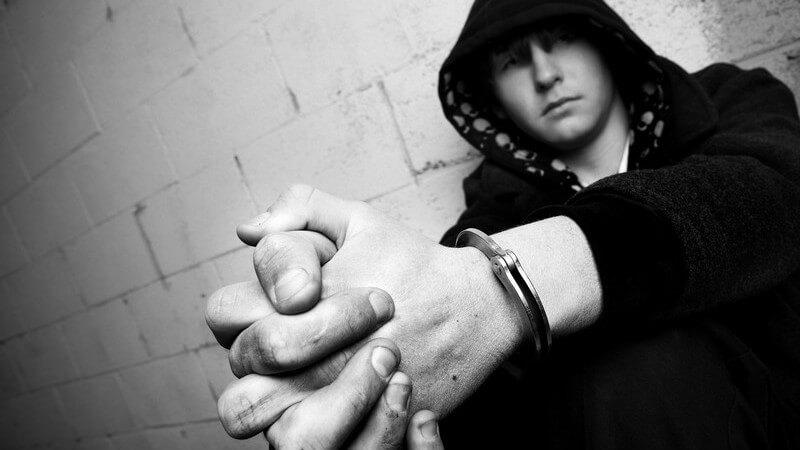 Schwarz-weiß Bild Jugendlicher in Kapuzenpulli hockt an Mauer, Hände in Handschellen