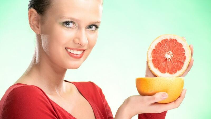 Blonde lächelnde Frau hält halbierte Grapefruit in Kamera