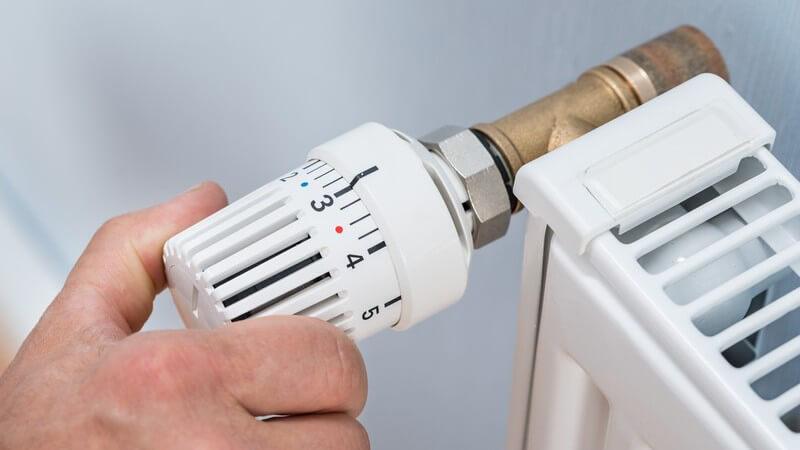 Thermostatknopf eines klassischen Heizkörpers wird auf Stufe 3 gedreht