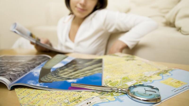 Junge Frau mit Reiseführer vorCouch, vor ihr  Landkarte für Touristen und Lupe auf Tisch