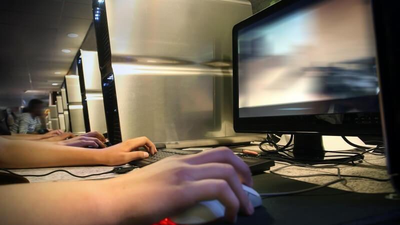Computer in einem Internetcafe, Hände sind an den Computermäusen und Tastaturen