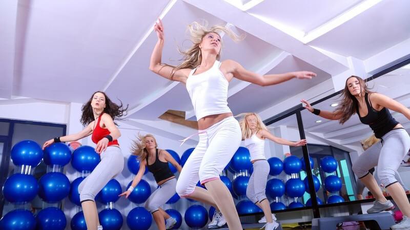 Gruppe von jungen Frauen beim Steppen in Fitnessstudio