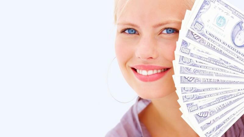 Blonde Frau lächelt in Kamera, hält Geldscheine vor Gesicht