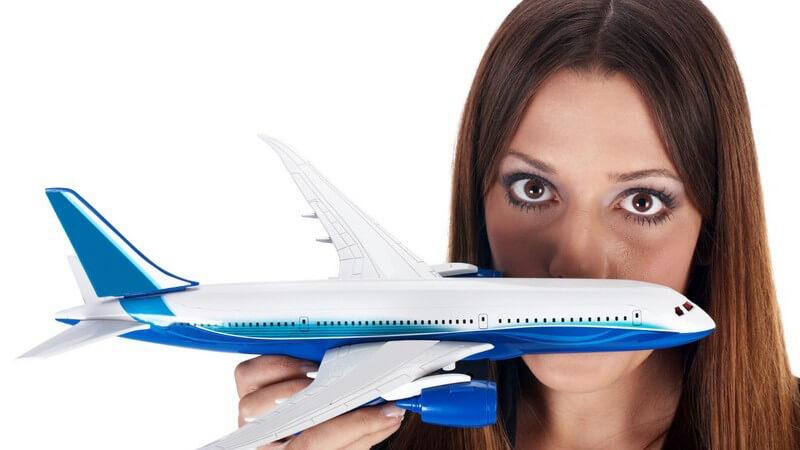 Junge dunkelhaarige Frau mit Flugangst hält Modellflugzeug in Hand und schaut ängstlich