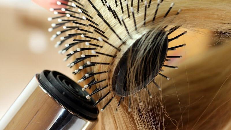 Nahaufnahme blonde Haare über Rundbürste werden geföhnt