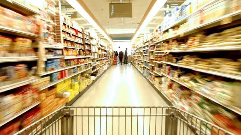 Einkaufswagen wird durch Gang im Supermarkt geschoben, am Ende Leute an der Kasse