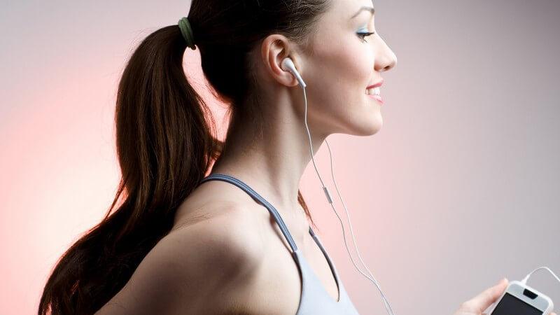 Junge Frau im Sportoutfit auf Laufband hört Musik über Kopfhörer