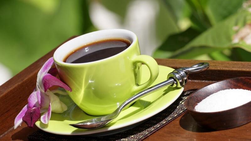 Nahaufnahme grüne Tasse Kaffee mit pinker Blüte
