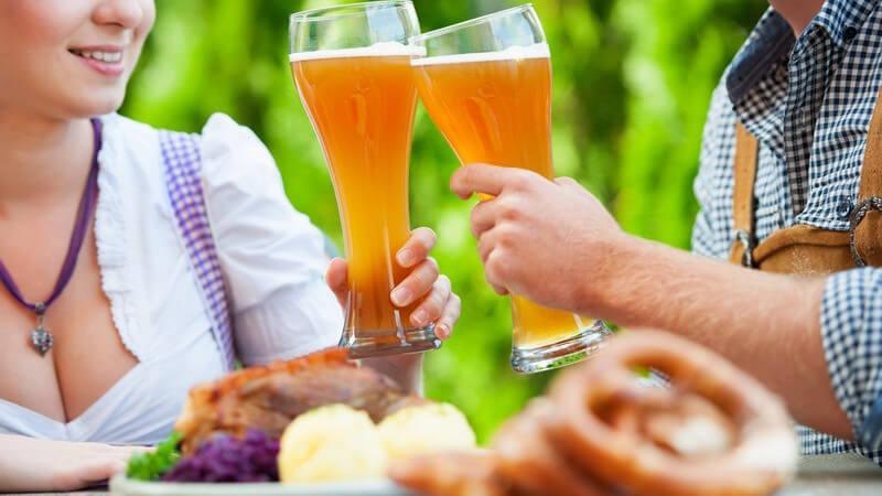 Paar in Trachtenkleidung (Dirndl, Lederhose) stößt mit Weizenbier an und isst zünftiges Gericht (Knödel)