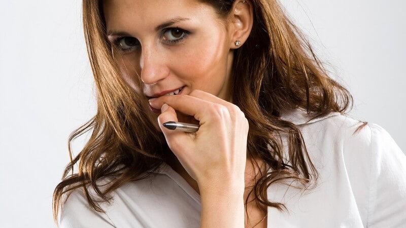 Junge Frau kaut nervös auf ihren Fingernägeln