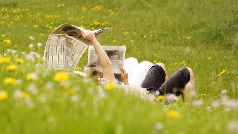 Junges Paar liegt auf Wiese und liest Zeitung