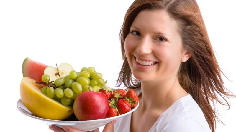 Junge Frau trägt Teller mit frischem Obst, lacht in Kamera