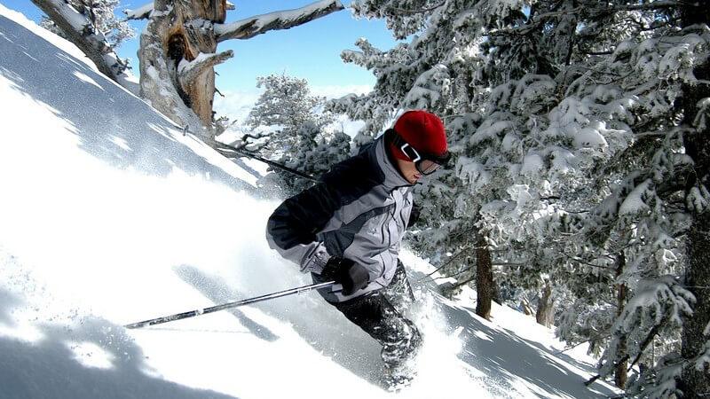 Junger Skifahrer fährt Hang im Wald hinunter