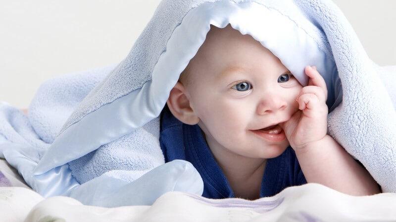Baby liegt unter einer blauen Kuscheldecke und nuckelt am Daumen