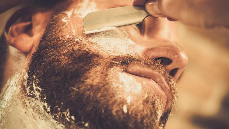 Junger Mann mit Vollbart bekommt von einem Barbier den Bart mit einem Rasiermesser abrasiert, Ansicht von unten