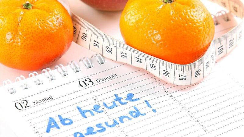Mandarinen und Maßband auf Kalender: Abnehmen, Vorsatz