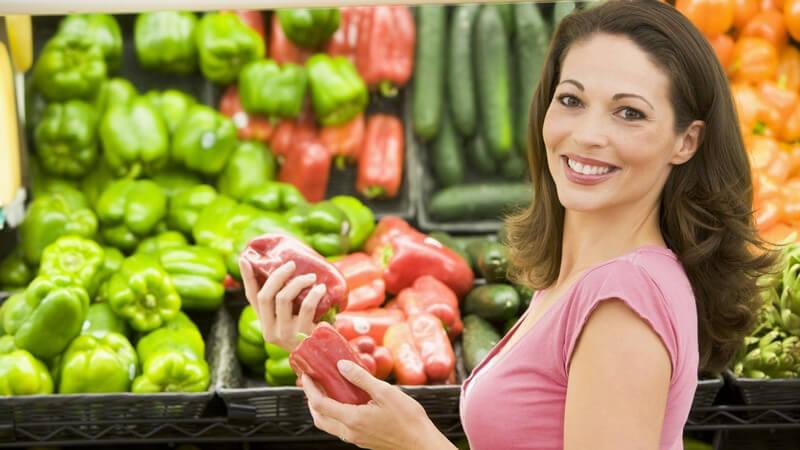 Junge Frau im Supermarkt hält Paprika in Händen