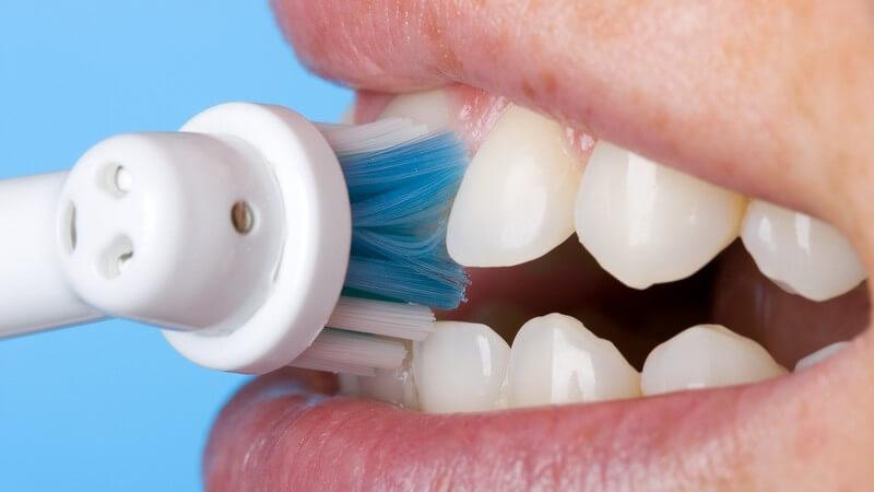 Zähne - Putzen der Schneidezähne mit elektrischer Zahnbürste