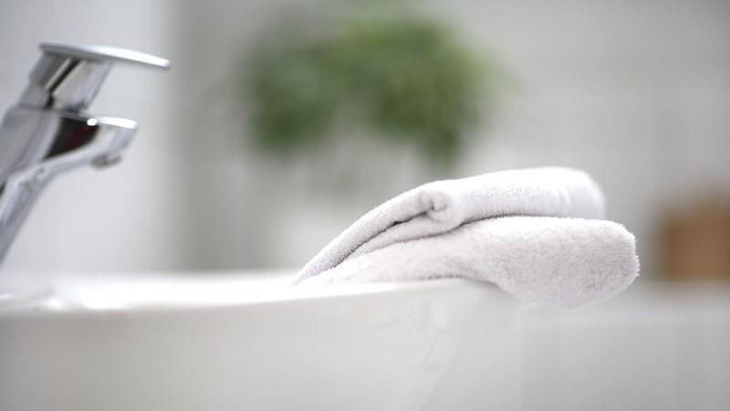 Zwei zusammengelegte weiße Handtücher liegen auf Rand des Waschbeckens