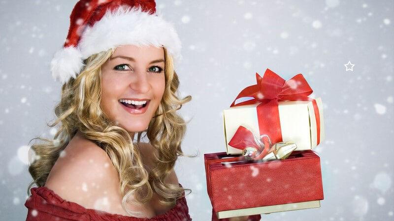 Blond gelockte Frau in Weihnachtskostüm hält 2 Geschenkpakete hoch