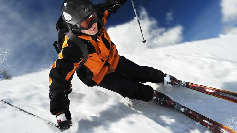 Skifahrer mit Helm und Skibrille carvt unter blauem Himmel eine Piste hinunter