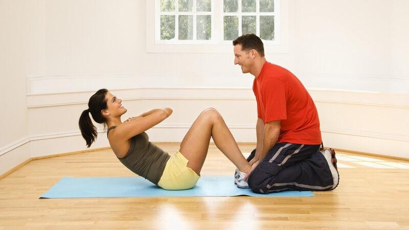 Frau macht Situps, Mann in rotem T-Shirt hält ihre Füße am Boden