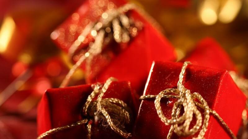 Kleine rot eingepackte Geschenke mit goldener Schnur