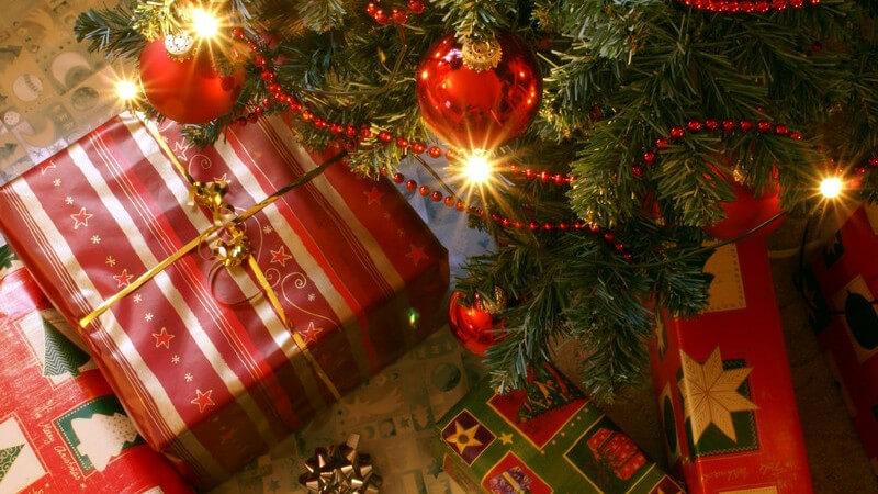 Geschenke unter einem Christbaum mit roten Kugeln