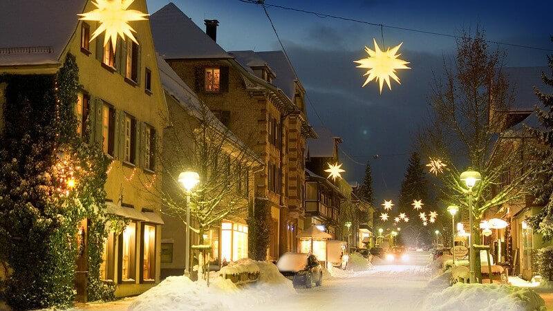 Beleuchtete Straße mit Weihnachtssternen und Schnee auf der Straße