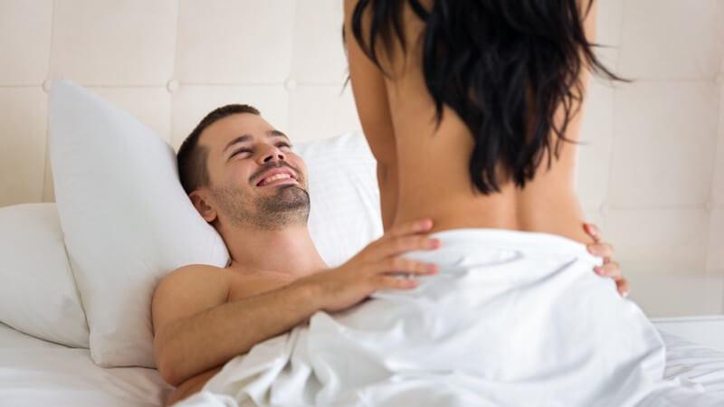 Paar beim Sex im Bett, sie sitzt auf ihm, er hält ihre Hüften