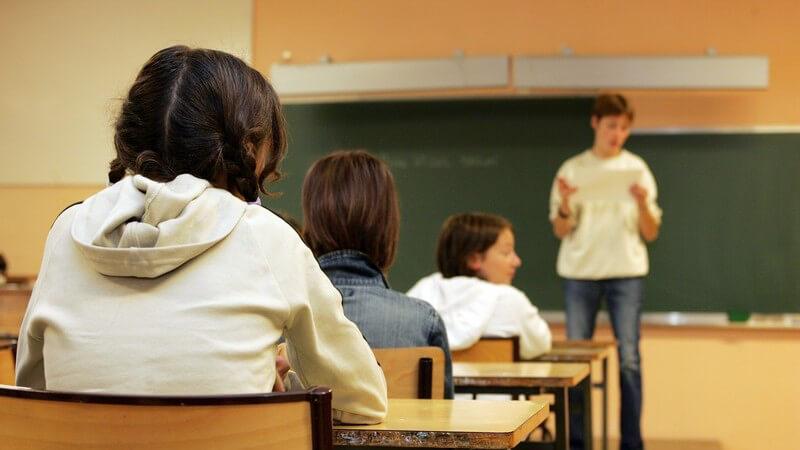 Lehrer vor der Tafel, 3 Reihen Schulkinder an ihren Bänken, von hinten fotografiert