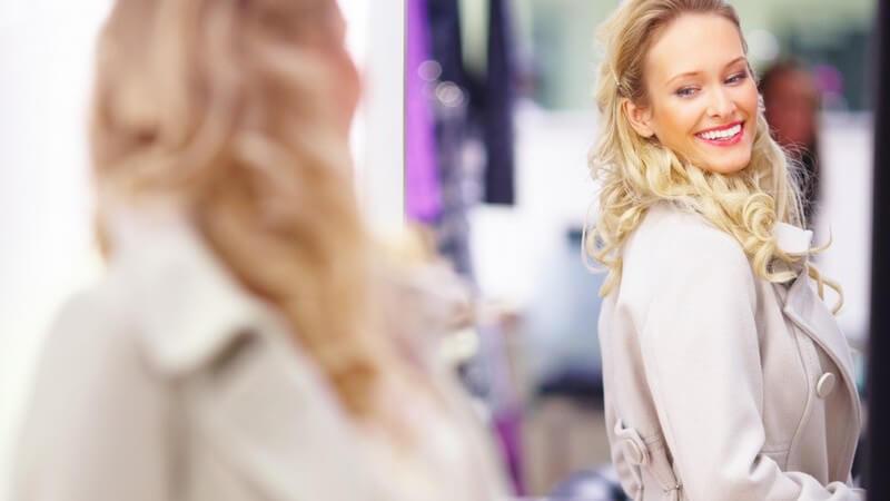 Frau probiert Mantel im Geschäft an, steht vor dem Spiegel