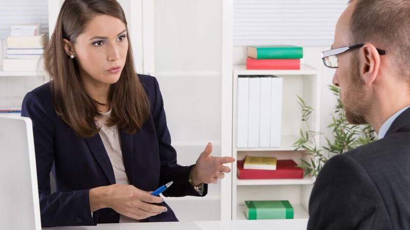 Junge Frau in Businesskleidung im Gespräch mit einem Kunden im Anzug, weißes Büro