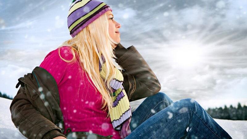 Junge Frau mit Mütze sitzt im Schnee