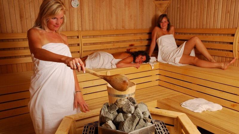 Drei Freundinnen in Sauna, eine macht Aufguss auf heißen Steinen