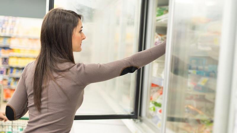 Junge Frau nimmt im Supermarkt Tiefkühlkost aus einem Gefrierschrank