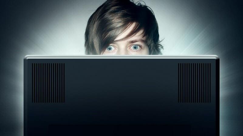 Obere Gesichtshälfte eines jungen Mannes, starrt auf Computerbildschirm