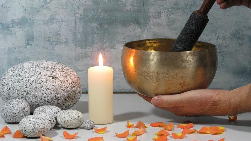 Goldene Klangschale neben weißer Kerze, Steinen und Blütenblättern