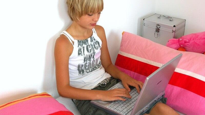 Blondes, kurzhaariges Mädchen neben rosa Kissen mit Laptop auf dem Schoß