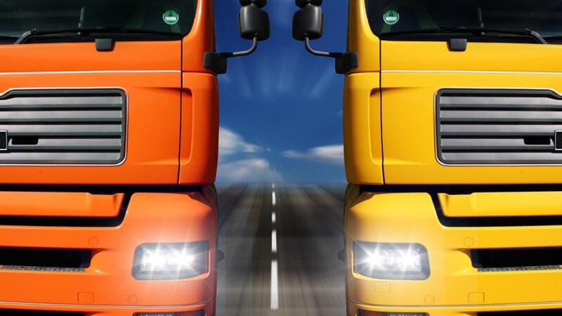Orangener und gelber LKW nebeneinander auf Straße