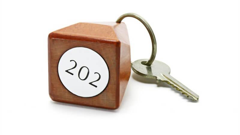 Hotelzimmerschlüssel mit Plakette mit Nummer auf Holzwürfel, vor weißem Hintergrund